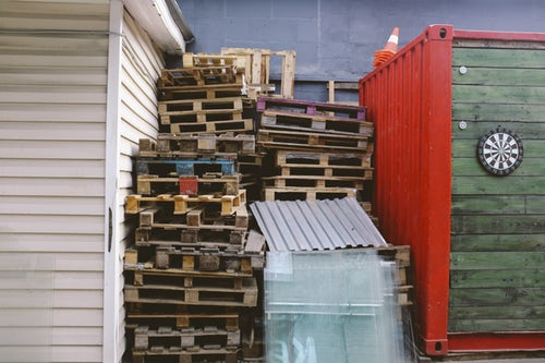 Large piled of heavy wooden pallets that will require mobile scissor lift tables to be moved