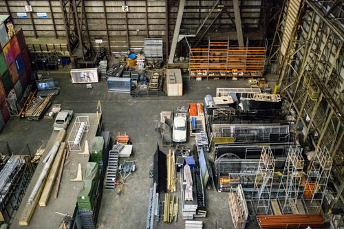Birdseye view of large loading area with mobile scissor lift tables parked next to storage containers